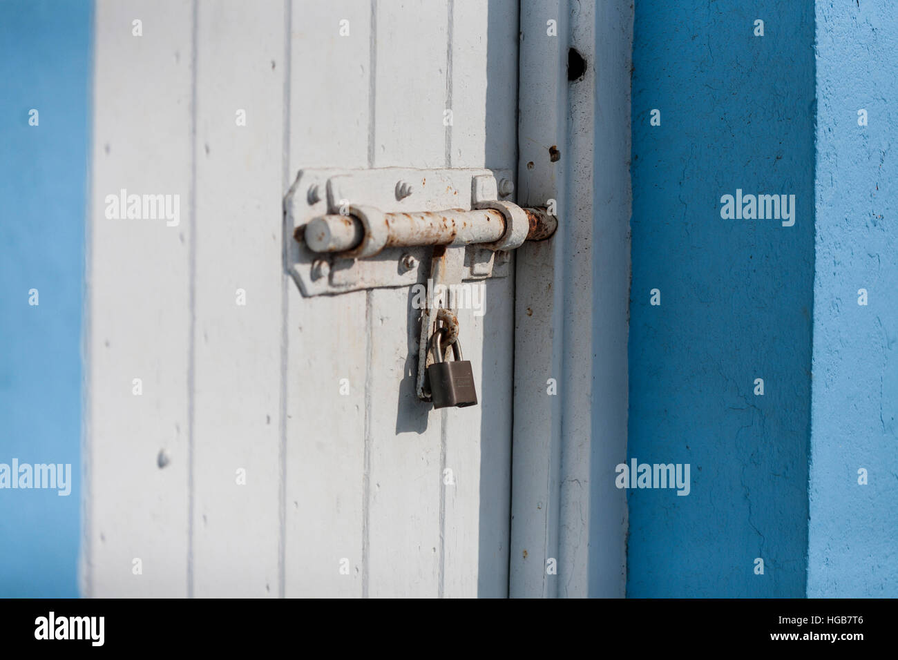 Pad Lock and heavy bolted door. A padlocked white door with a heavy rusting steel bolt holding it secure in a blue painted stucco building. . Hopetown & Pad Lock and heavy bolted door. A padlocked white door with a heavy ...