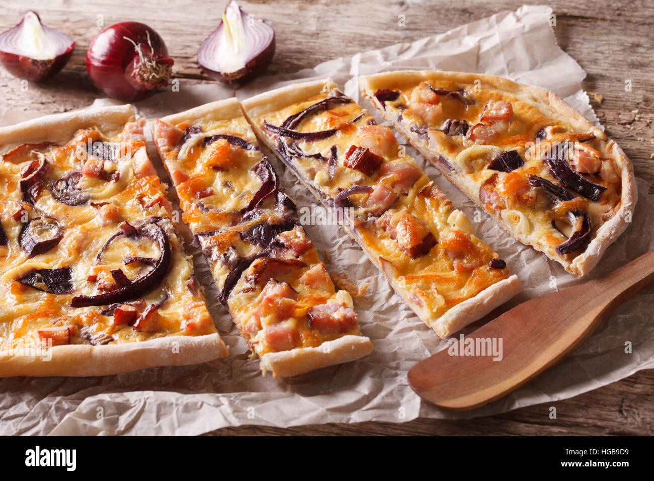 sliced pie flammkuchen with bacon and red onion on the paper. Horizontal closeup - Stock Image