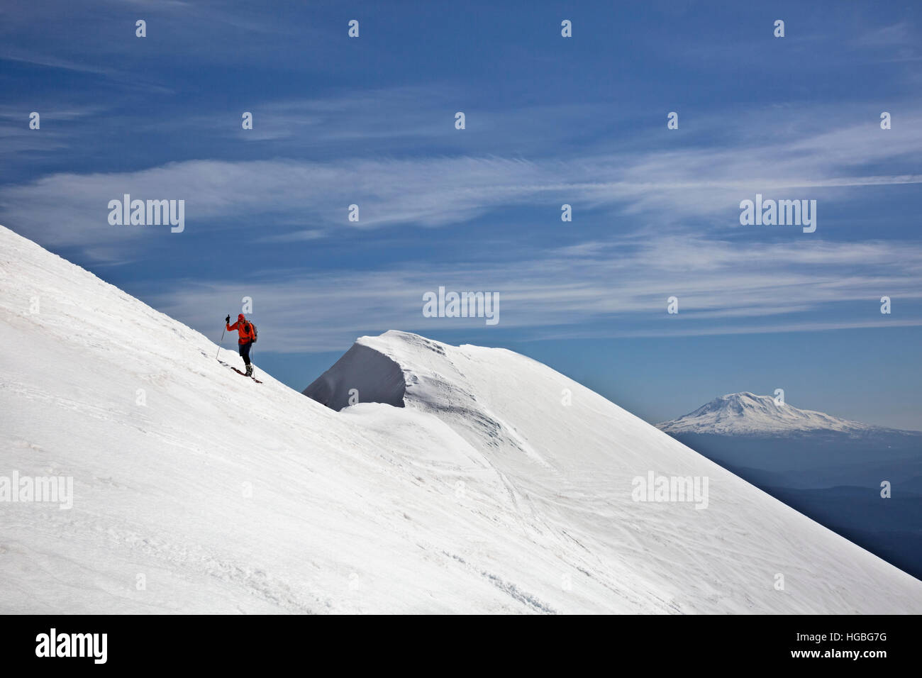 WA13127-00...WASHINGTON - Skiing the the rim of the crater on the summit of Mount St. Helens with Mount Adams in - Stock Image