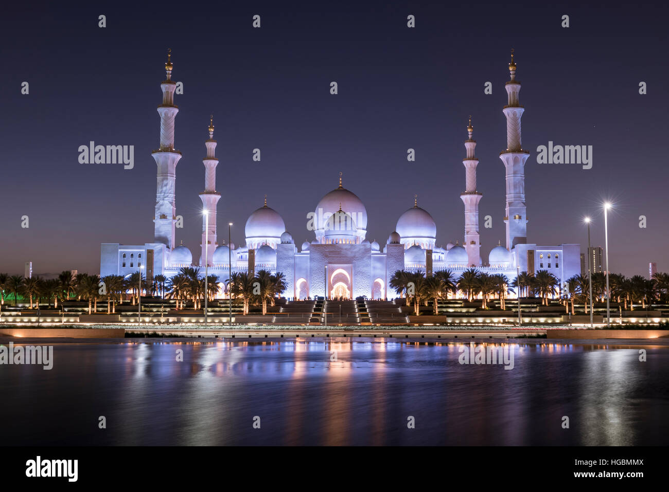 Sunset over the Sheikh Zayed Grand Mosque in Abu Dhabi, United Arab Emirates.  Mosque is built of white marble and - Stock Image