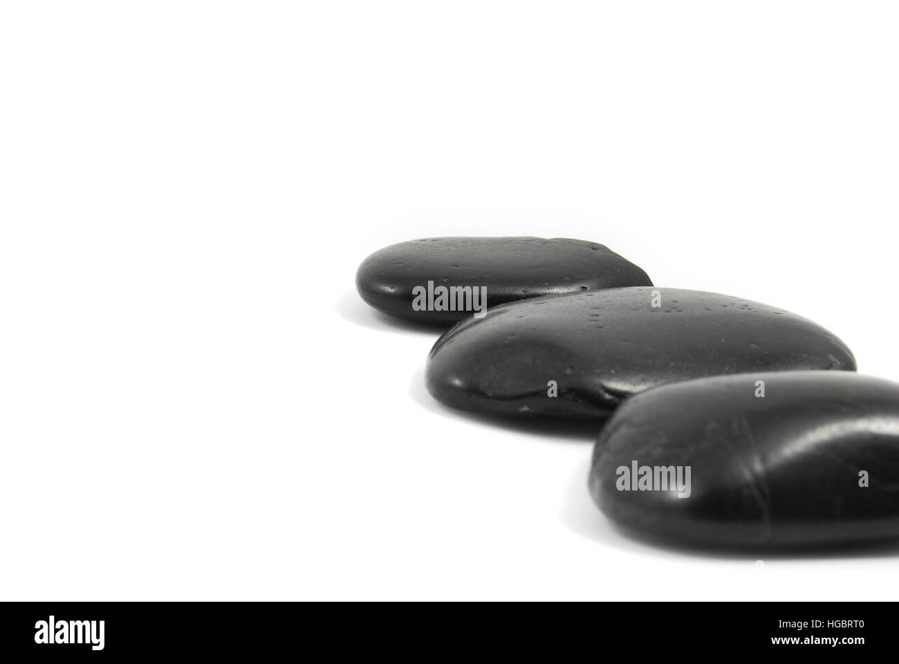 Three black stepping stones. Zen-like path leading one's eye into the future. - Stock Image