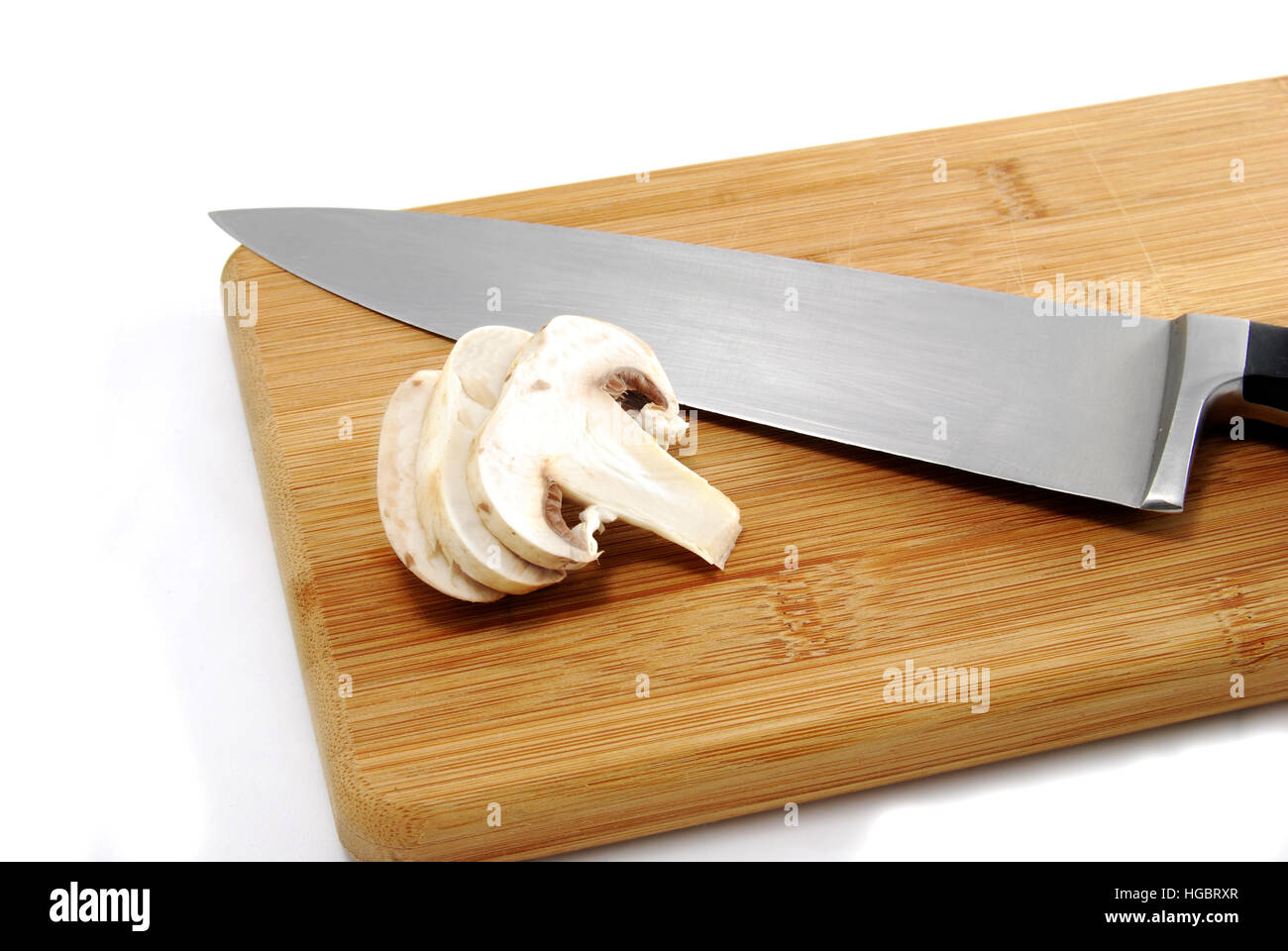 Preparing dinner by slicing mushrooms on cutting board. - Stock Image