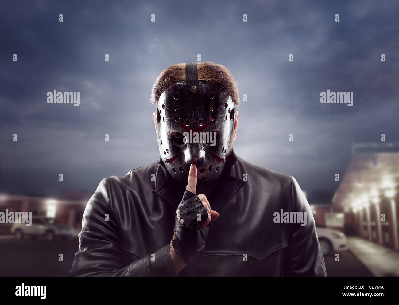 Bloody maniac in hockey mask show do not talk sign - Stock Image