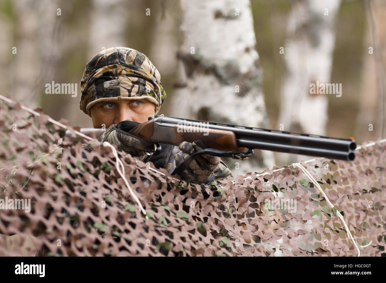 hunter aiming from behind camouflage netting - Stock Image
