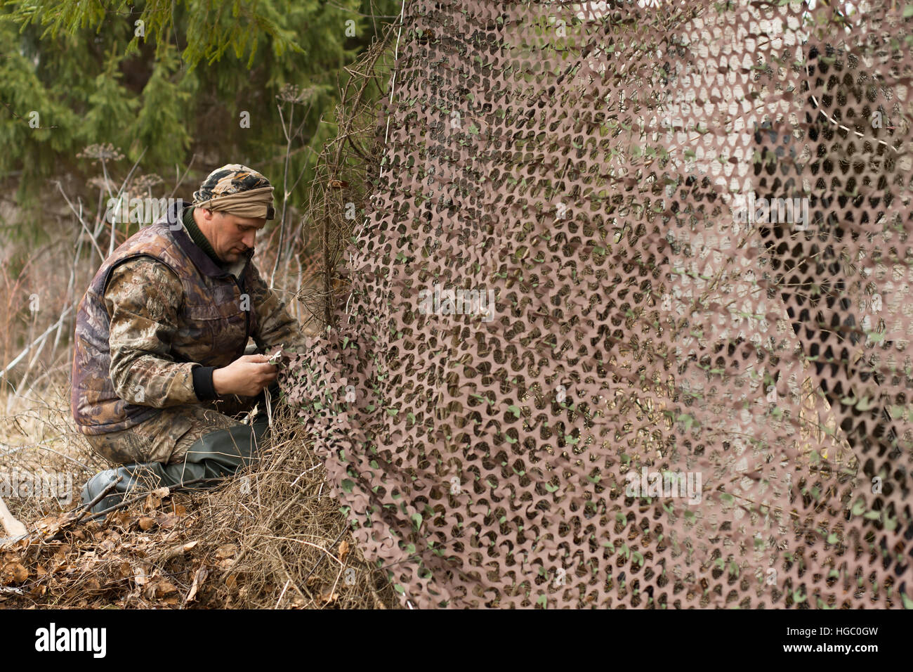 hunter and camouflage netting - Stock Image