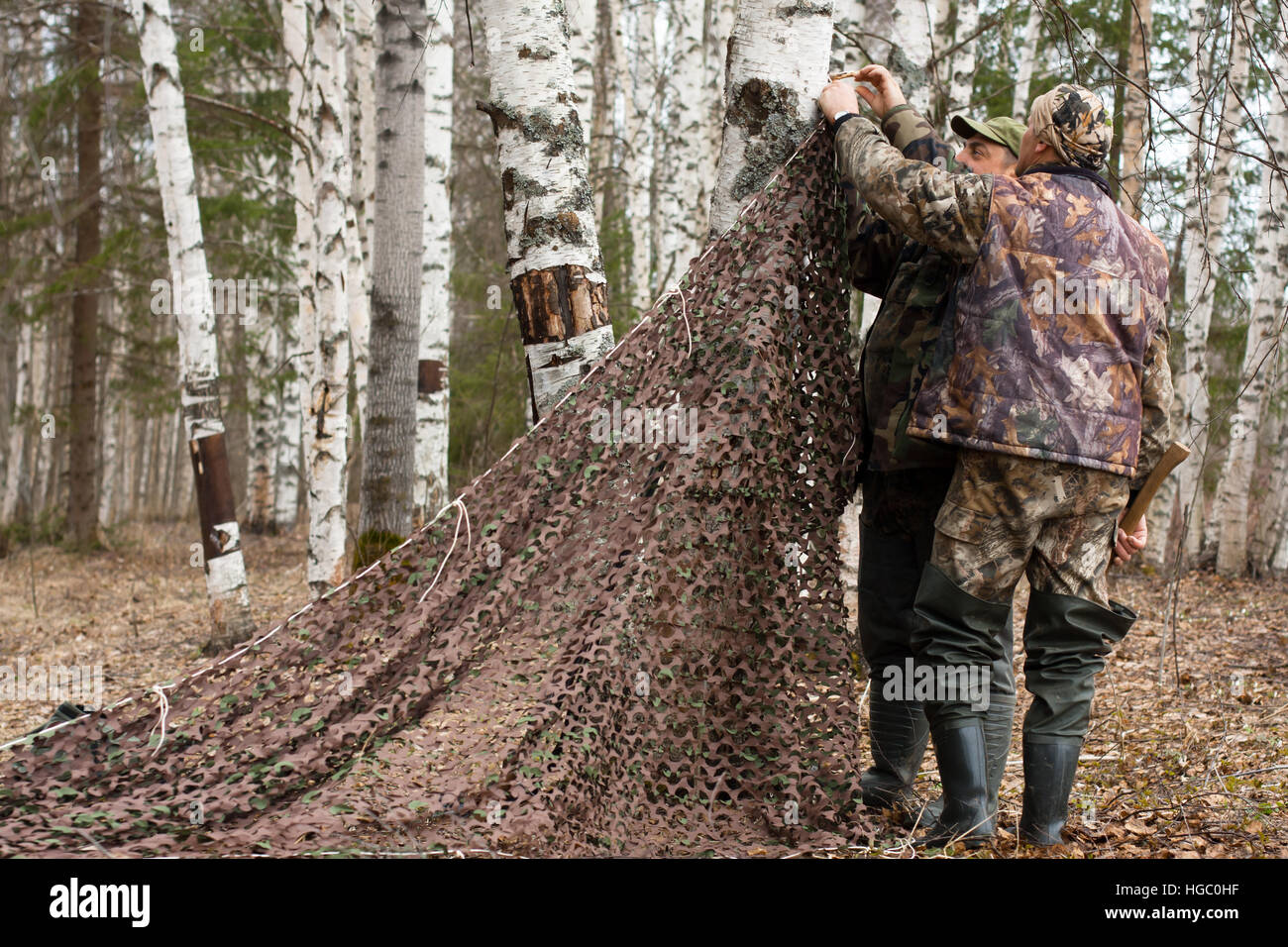 two hunters pull camouflage netting - Stock Image