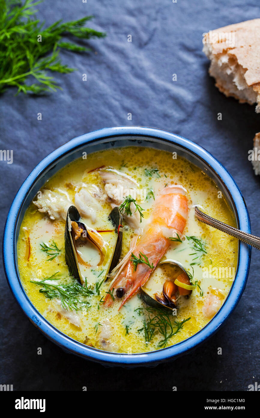 Scandinavian creamy fish soup with halibut, prawns and mussels - Stock Image