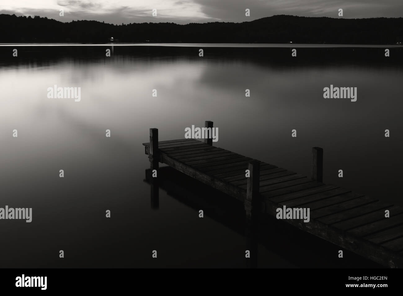 Old wooden jetty at night on a mirror calm lake with reflections and silhouettes long exposure monochrome - Stock Image