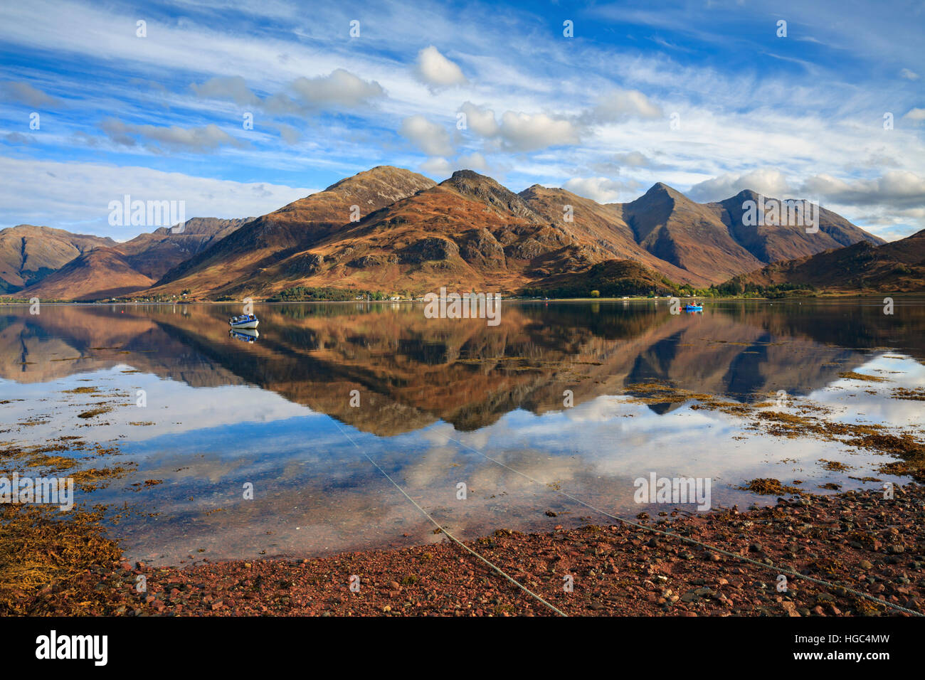 The Five Sisters of Glen Shiel reflected in Loch Duich. - Stock Image
