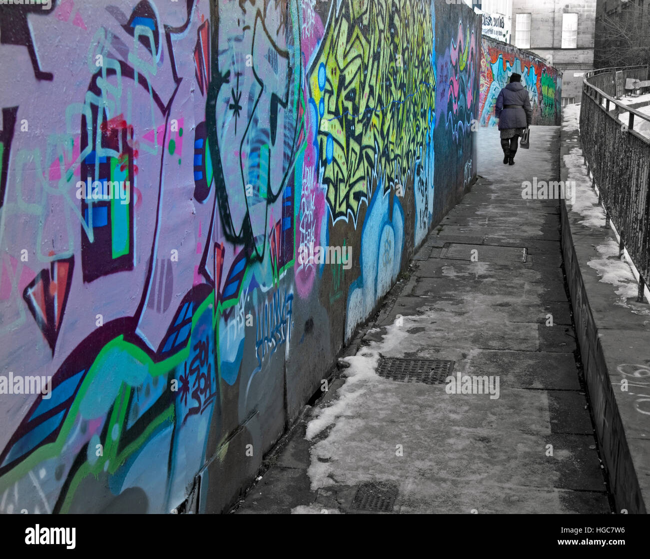Old lady walking down a snowy path with graffiti, Edinburgh City,Scotland - Stock Image