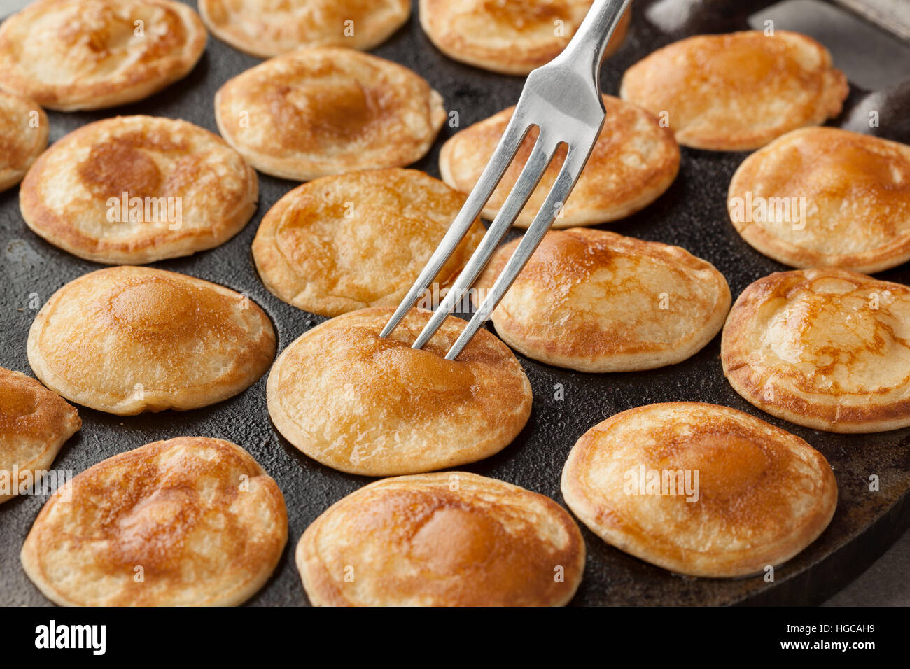 Baking Dutch mini pancakes called poffertjes in a special skillet pan - Stock Image