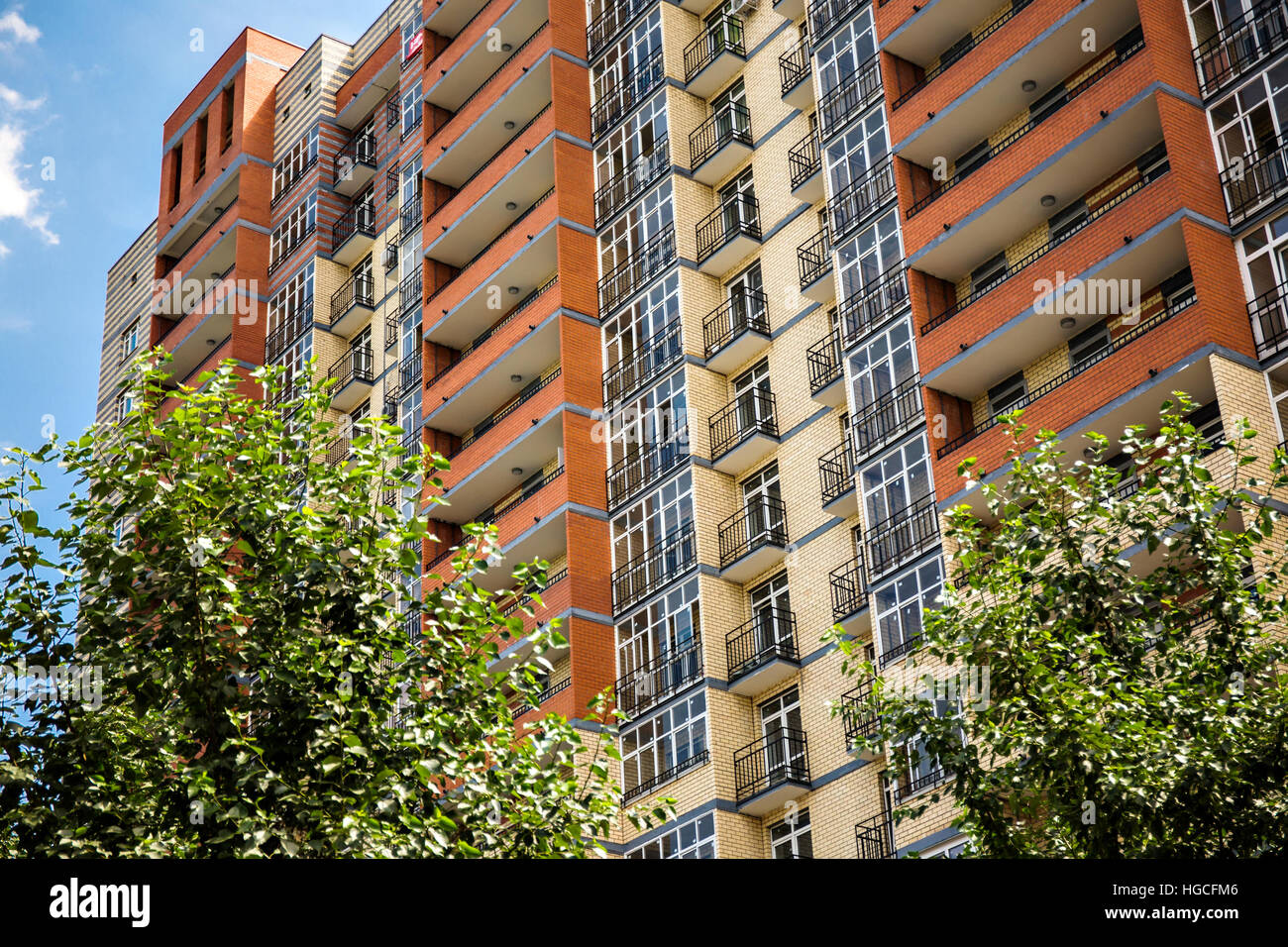 New modern multistorey apartment building with tree on the foreground - Stock Image