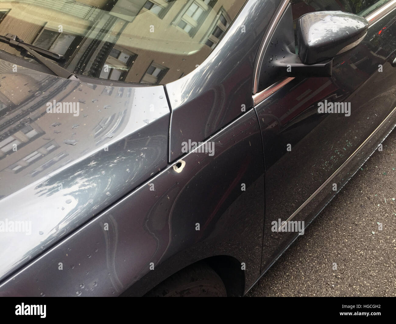 A bullet entered the fender of a car parked in front of a senior citizen home during a drive by shooting in Chicago. - Stock Image