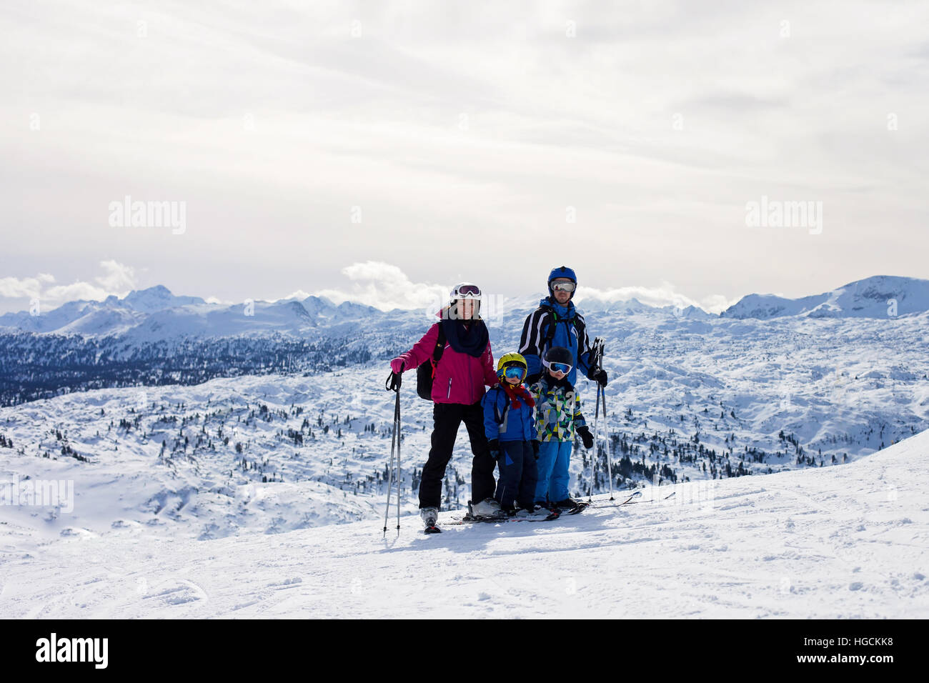 Young happy family with two childrens, boy brothers, skiing in Austrian ski resort on a sunny winter day - Stock Image