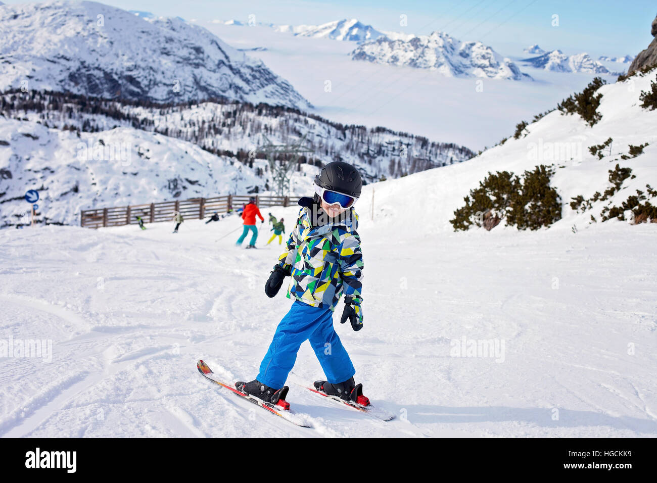 Cute little boy, skiing happily in Austrian ski resort in the mountains, wintertime - Stock Image