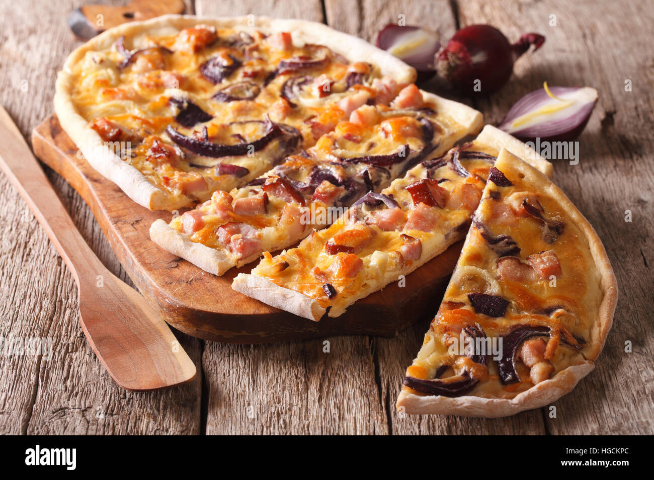 Delicious sliced pie flammkuchen with bacon and red onion close-up on the table. horizontal - Stock Image