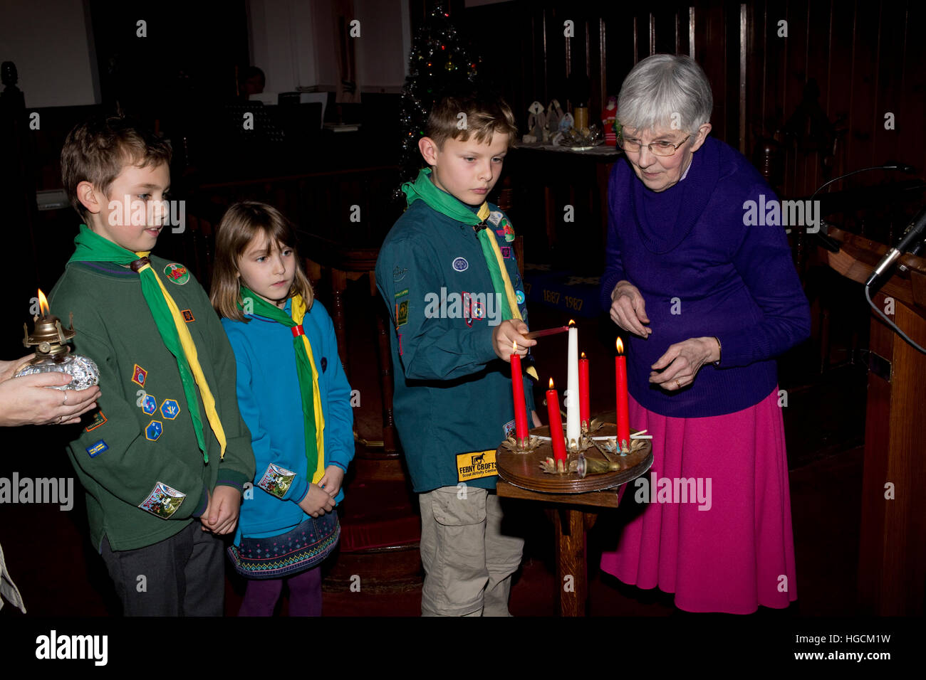 Boy scout lighting advent candles from the Bethlehem Light Mickleton Methodist Church UK - Stock Image
