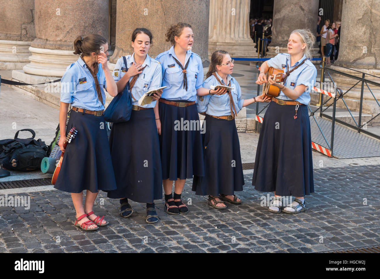A group of girls in uniform singing religious songs from the pantheon columns, Rome,  capital of Italy and  Lazio - Stock Image