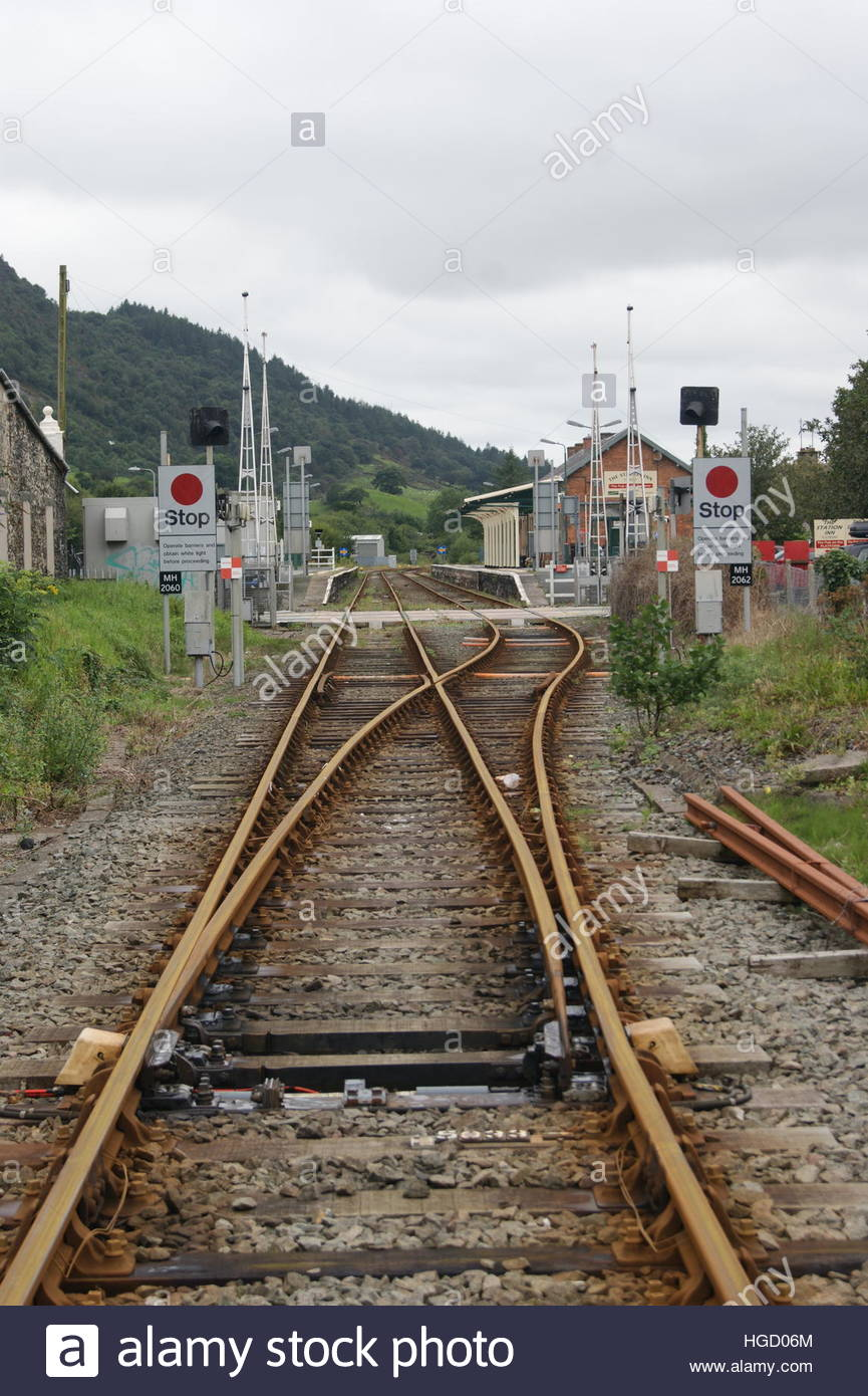 An end on view of Porthmadog mainline railway station and level crossing taken from a position further up the line. Stock Photo