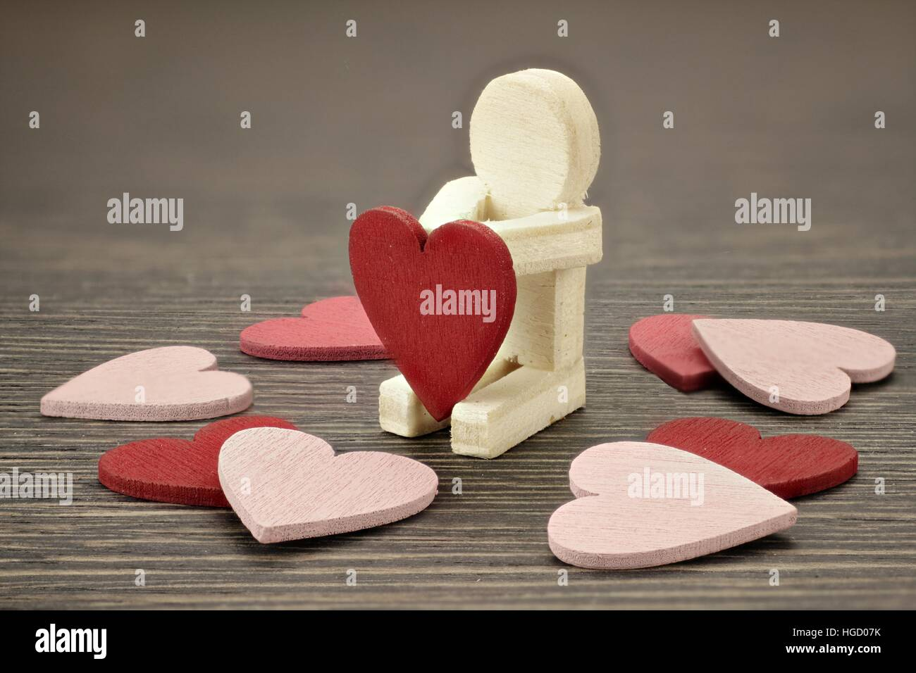 Wooden man with many red and pink hearts - Stock Image