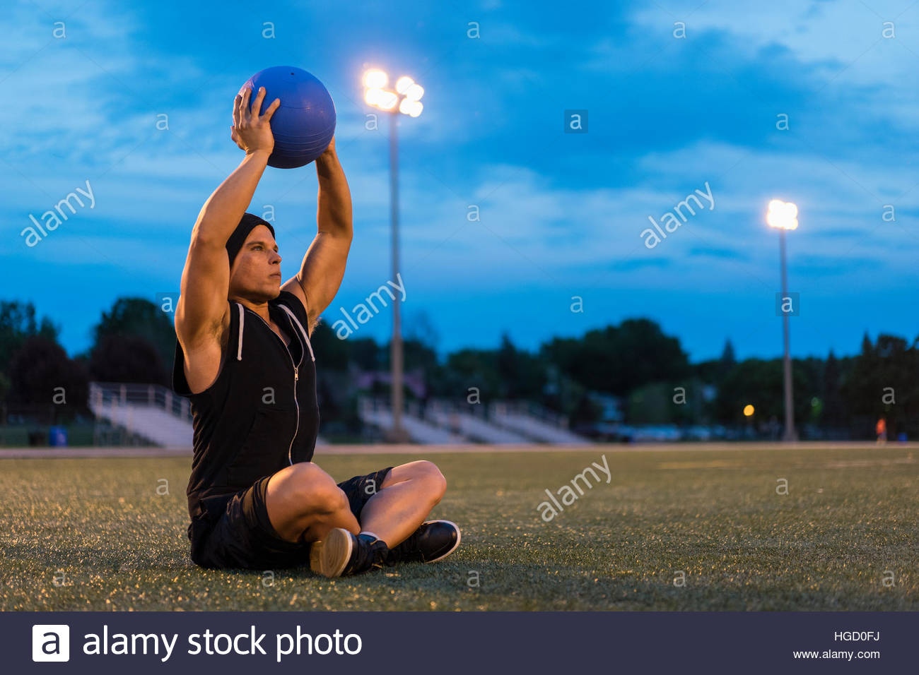 Athletic man using medicine ball during work out at night, Montreal, Quebec, Canada - Stock Image