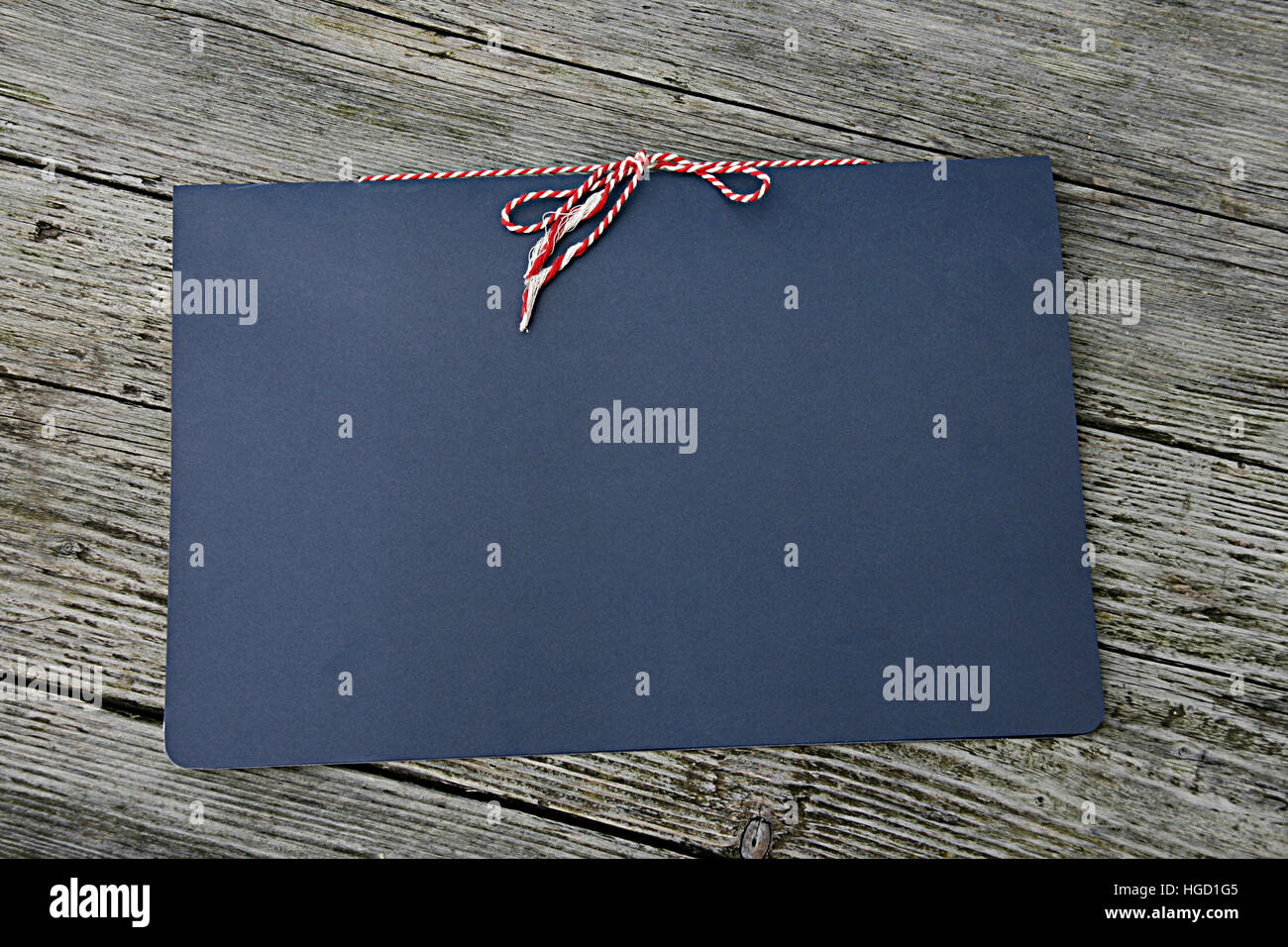 Blue folder on a wooden background with a red and white string tied bow. - Stock Image