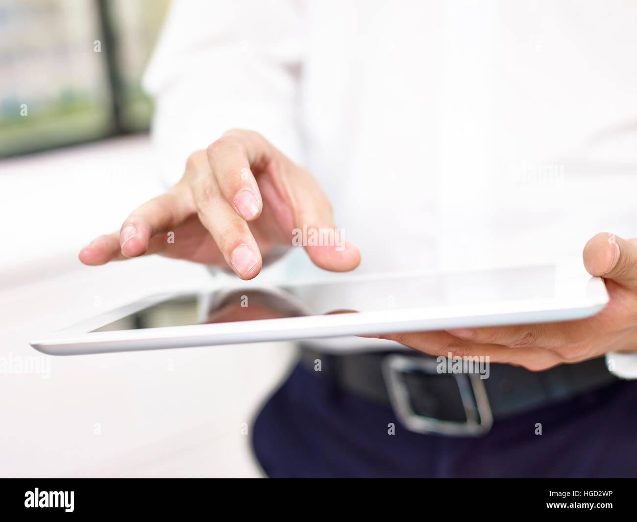 close-up of hands and fingers of a business man tapping the screen of a tablet computer. - Stock Image