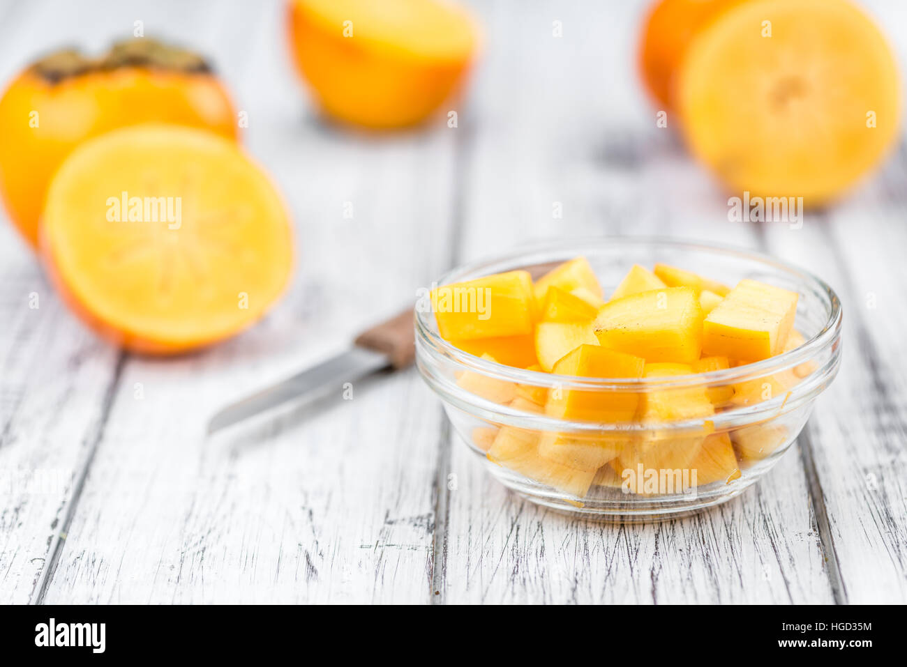 Fresh made Kakis on an old and rustic wooden table (selective focus, close-up shot) - Stock Image