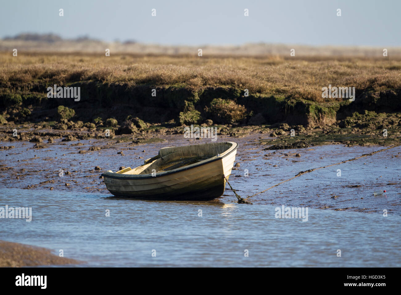 Small wooden dinghy boat moored on mudflats at low tide in Norfolk - Stock Image