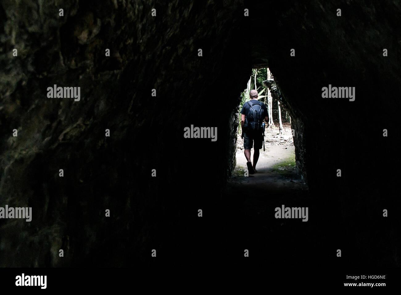 Men walking tunnel Coba Mayan Ruins in Mexico Yucatan - Maya religion - Stock Image