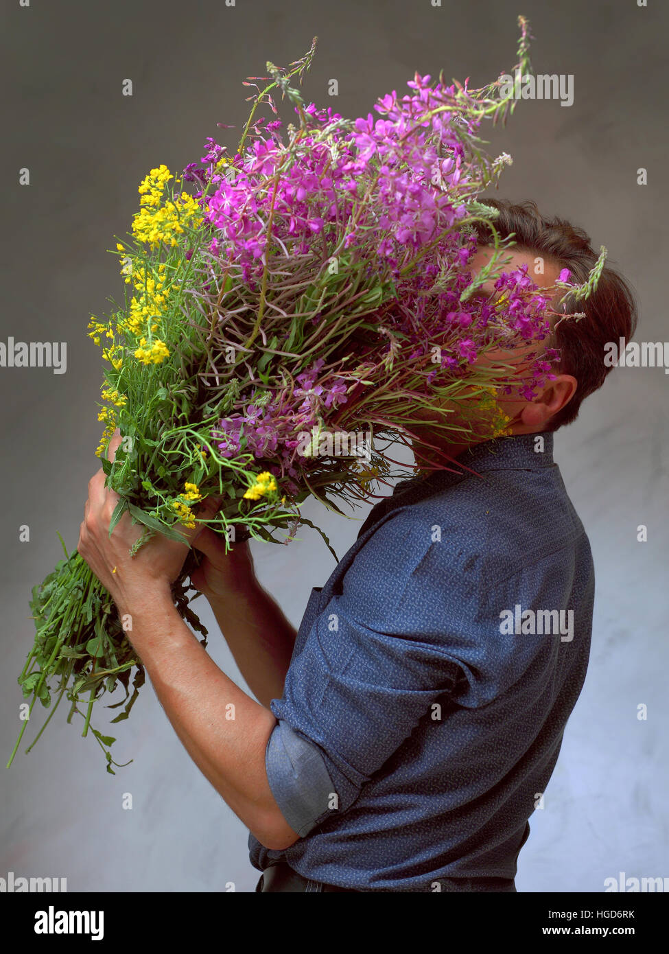 man holding a huge bouquet of wildflowers, a man came out on a date with flowers, man waiting for his love - Stock Image