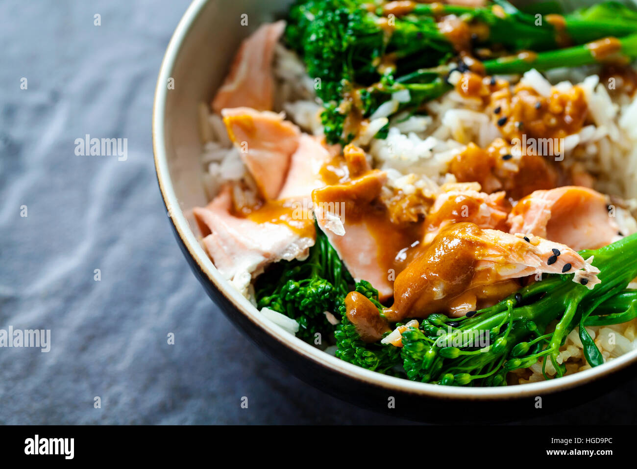 Poached salmon with rice, broccoli and miso sauce - Stock Image