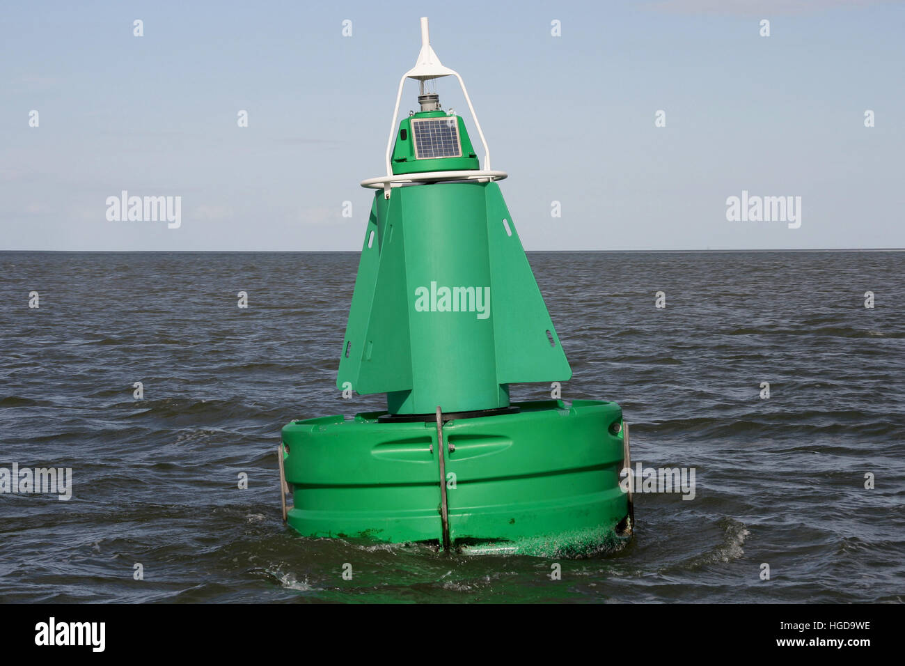 A green channel marker buoy in the water. - Stock Image