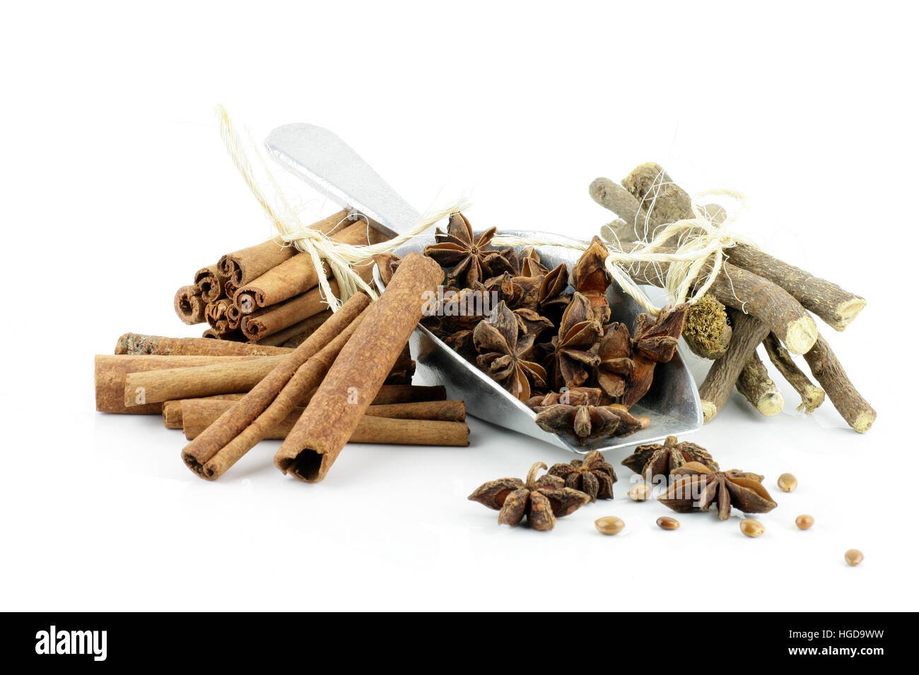 Star anise in an aluminium grocery scoop with cinnamon sticks and liquorice root. - Stock Image