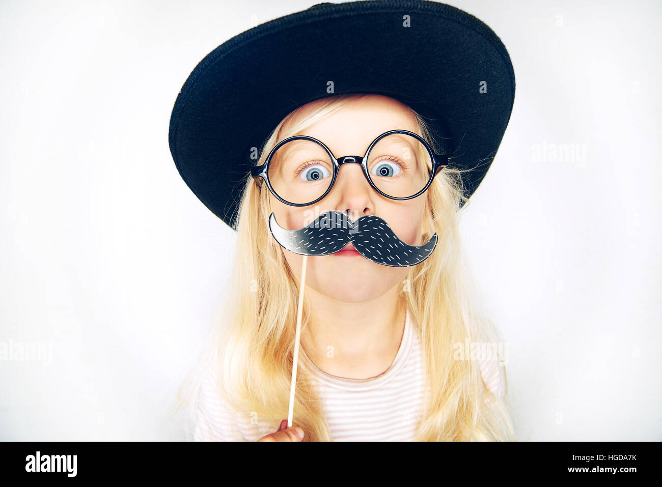 920b99c3b6c Little girl wearing black hat and glasses holding fake moustache on stick  and looking at camera