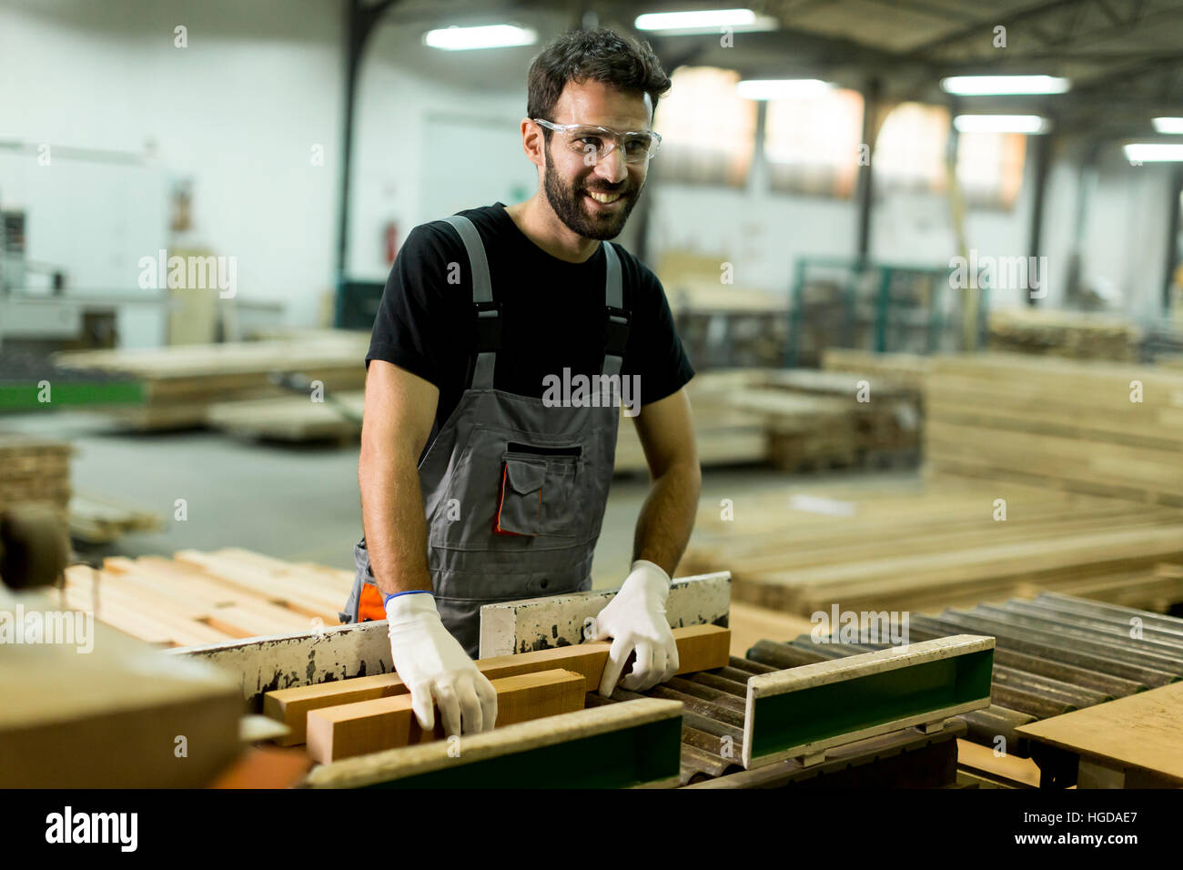 Handsome young man working in the furniture factory - Stock Image