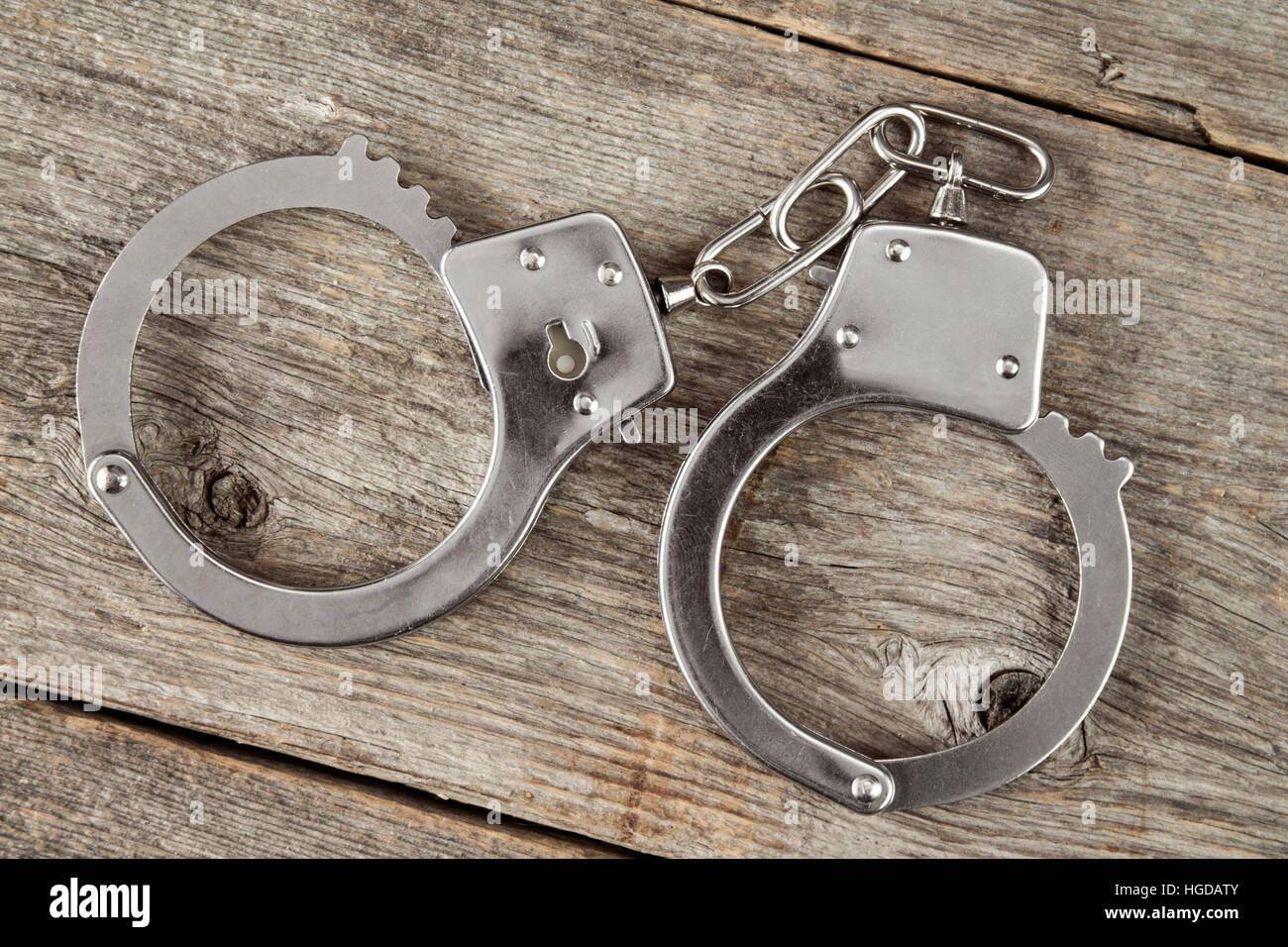 Top view of handcuffs on the wooden background - Stock Image
