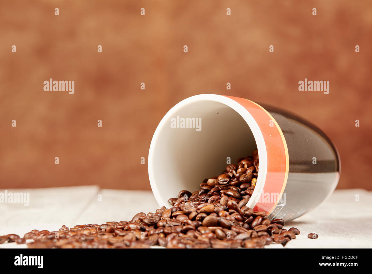 Table with scattered coffee beans and brown background - Stock Image