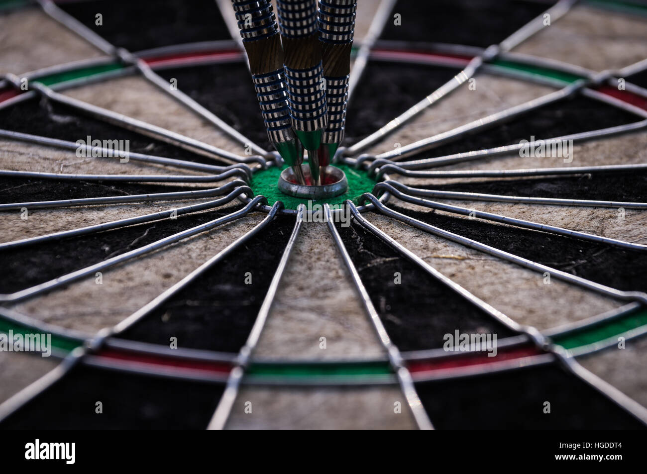 Three dart arrows hitting in the target center of dartboard - Stock Image