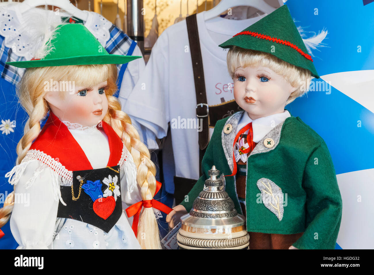 Germany, Bavaria, Munich, Souvenir Shop Window Display of Dolls in Bavarian Costume - Stock Image