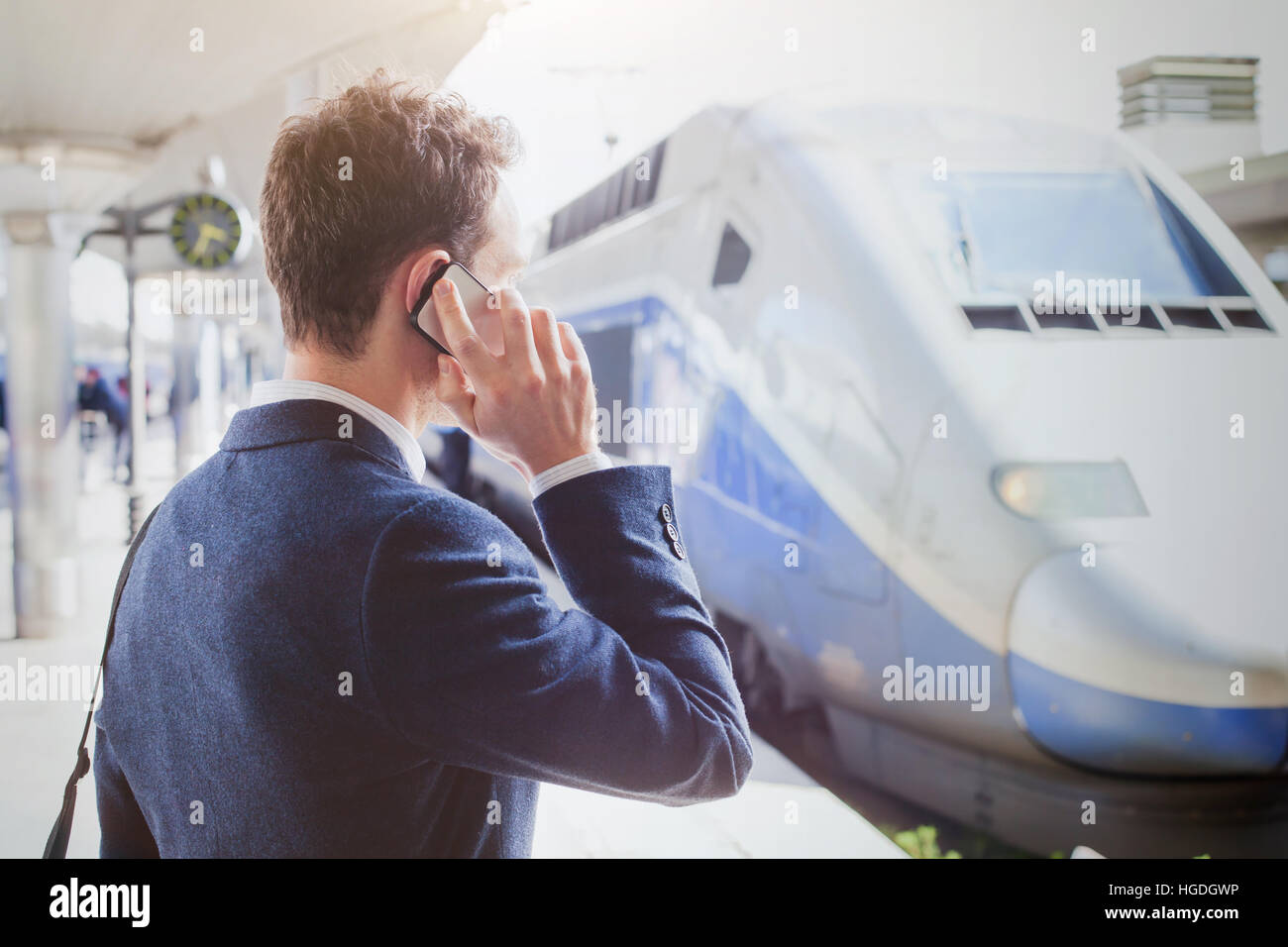 business travel, businessman talking by phone at the railway station while waiting for the train, mobile call - Stock Image