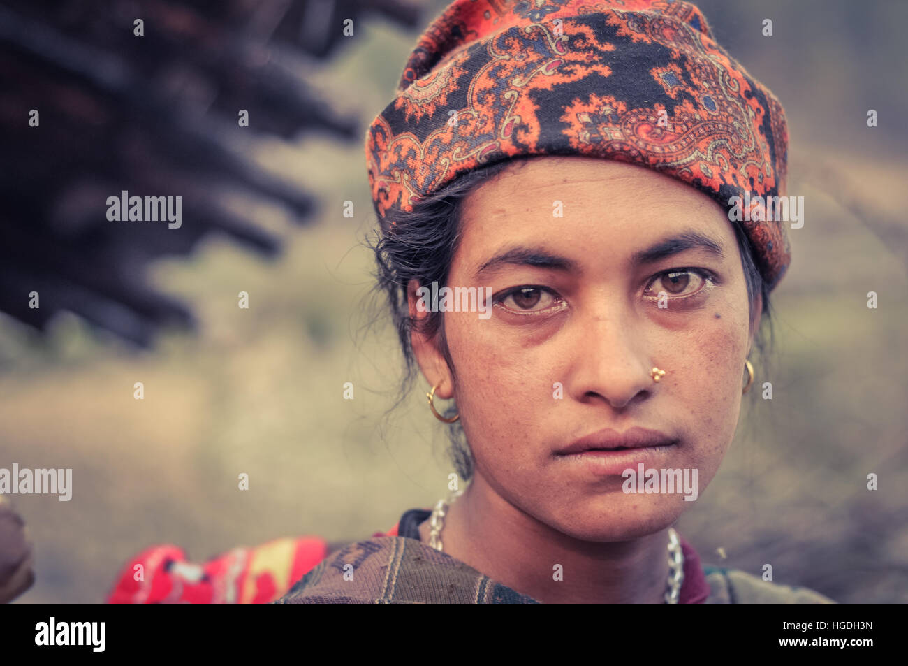 Dolpo, Nepal - circa May 2012: Native woman with piercing and earrings wears orange headcloth with brown eyes in Stock Photo