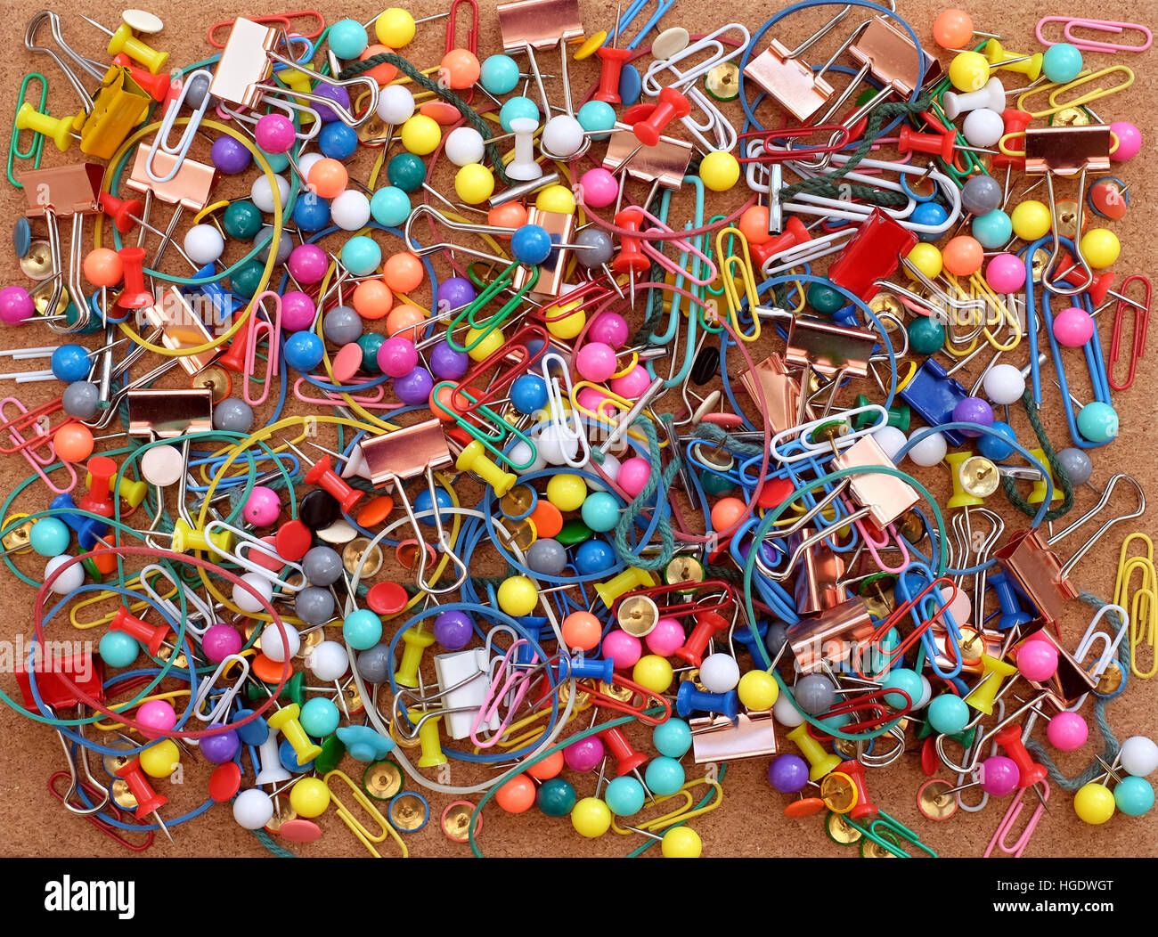stationery on cork background colorful paper clips rubber bands