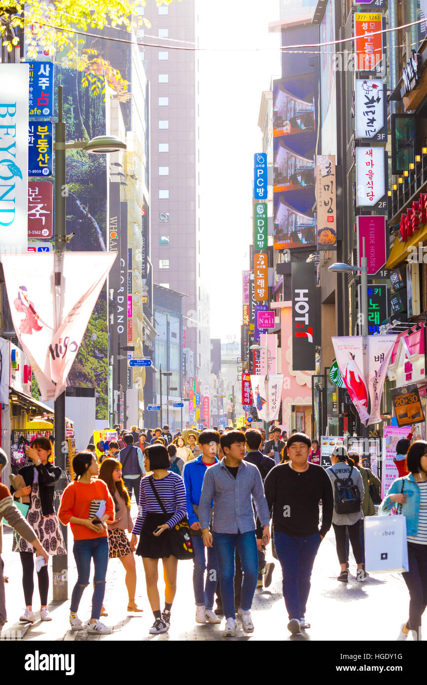 Young Koreans walking down busy backlit Myeongdong pedestrian shopping street with commercialism of many store signs - Stock Image