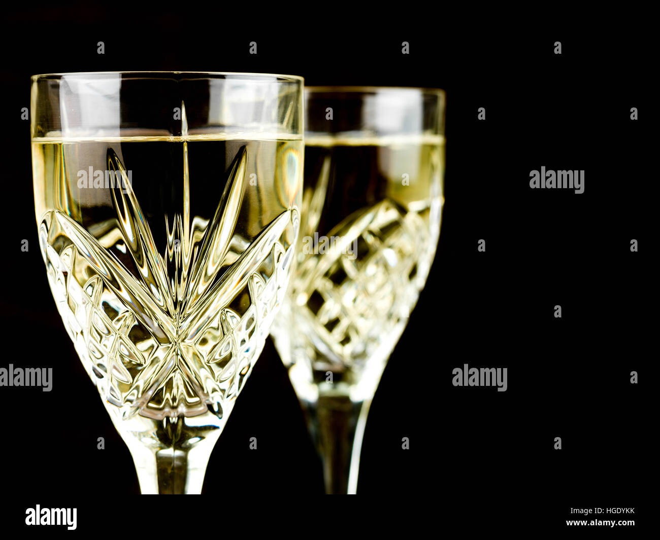 Chilled White Wine in a Cut Crystal Glass Against a Black Background Stock Photo
