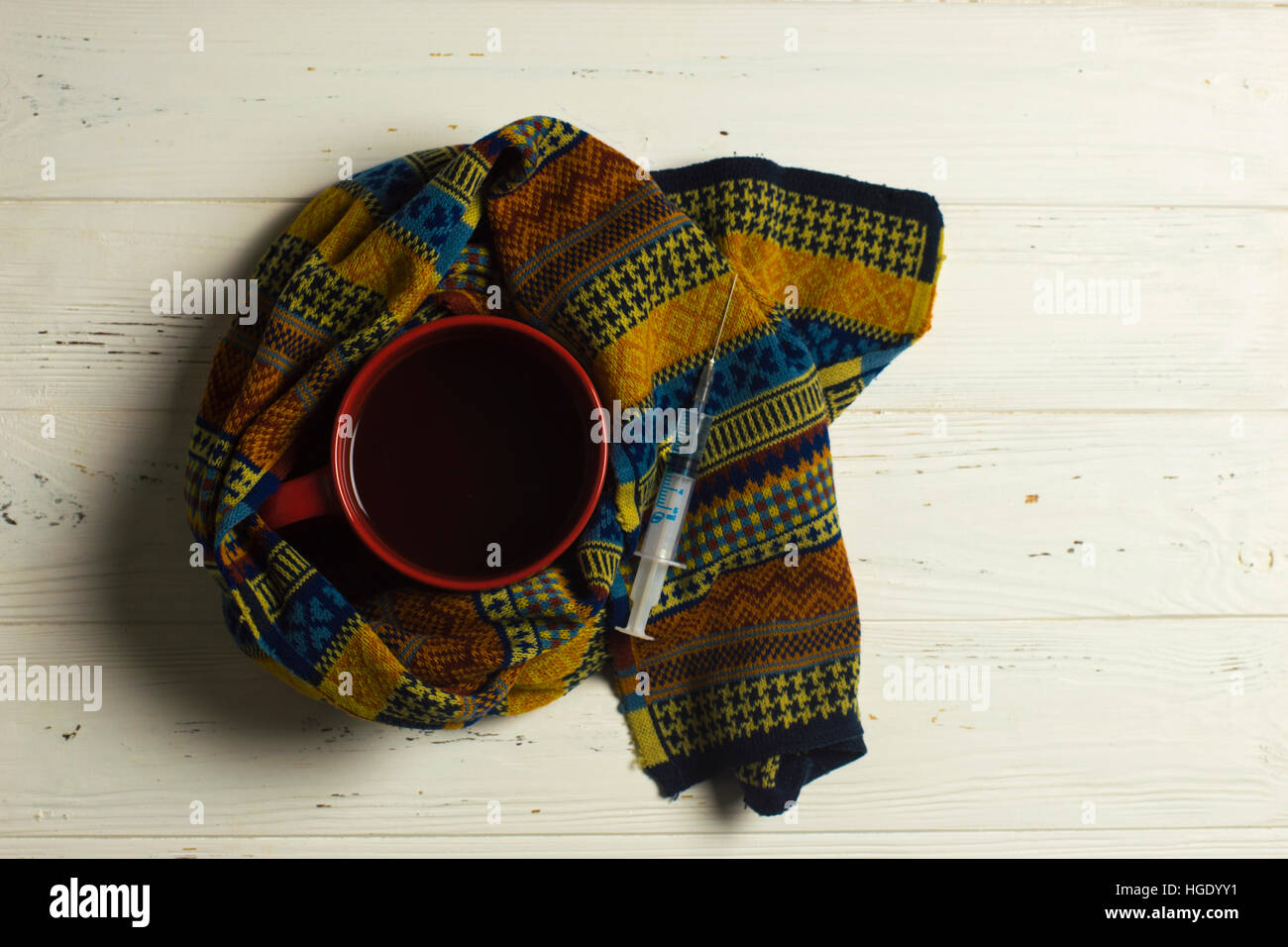 Teacup, scarf and syringe: winter illness safety concept - Stock Image