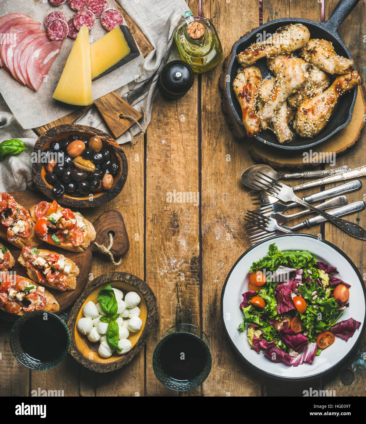 Rustic table set with meat, cheese, snacks, wine, copy space - Stock Image