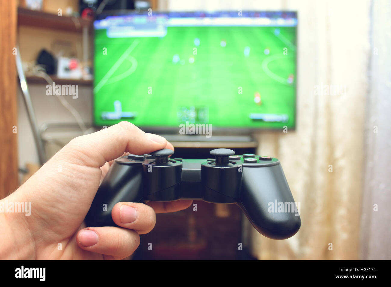 Playing football with the joystick on the game console - Stock Image