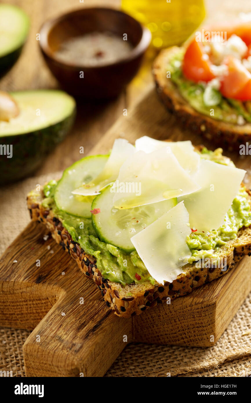 Avocado toast with cucumber and parmesan - Stock Image