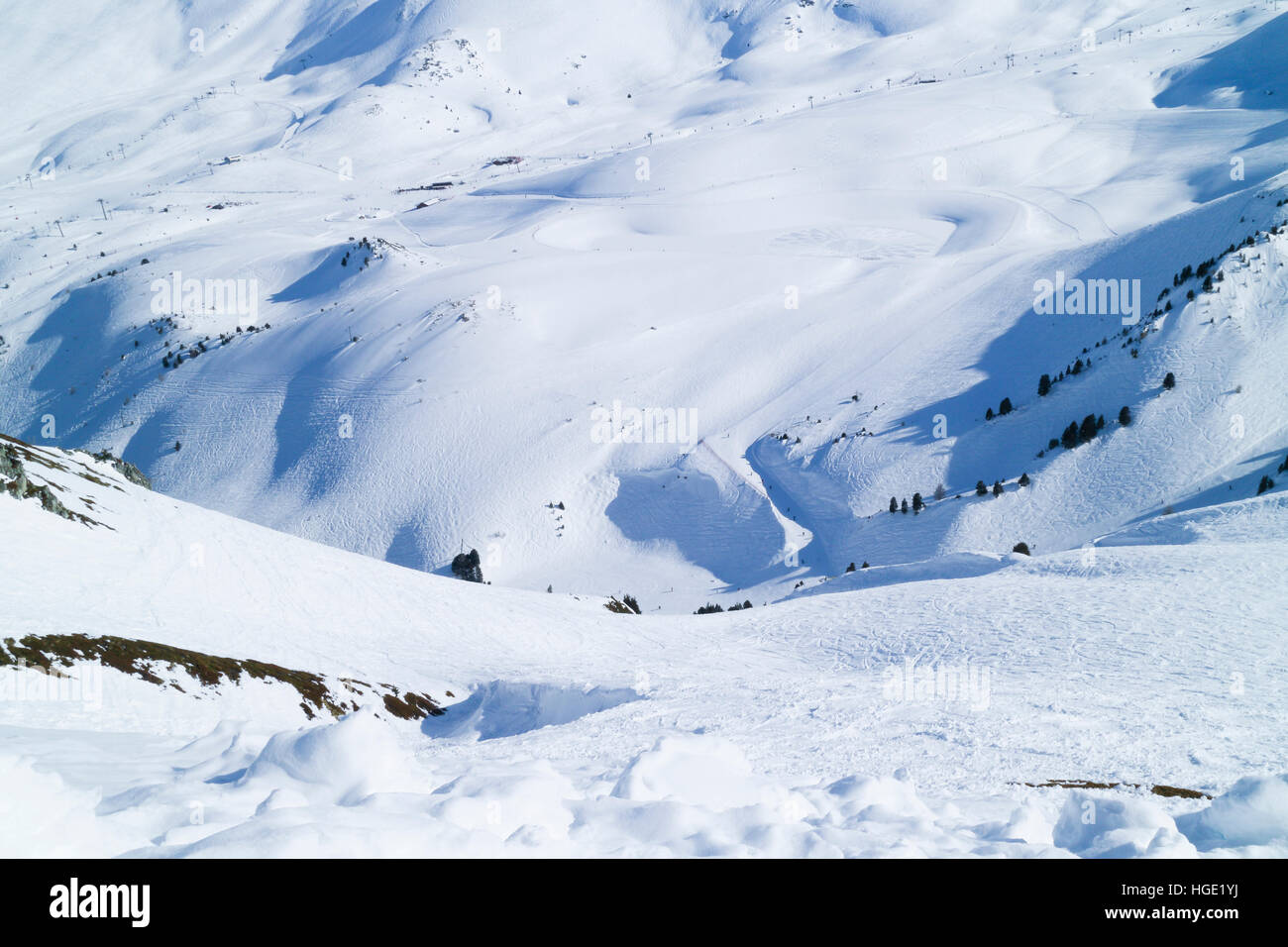 Snowy mountain valley crisscrossed by ski tracks on groomed slopes and off piste - Stock Image